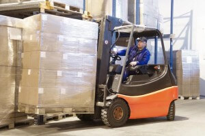 Stock photo of man operating a forklift lifting a large amount of packages