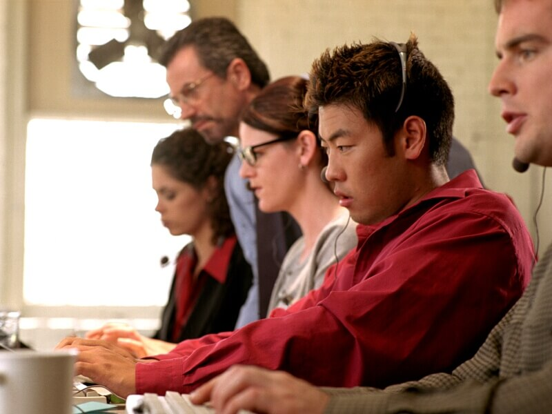 Stock photo of group of people training on keyboards, focusing on a screen (not pictured)